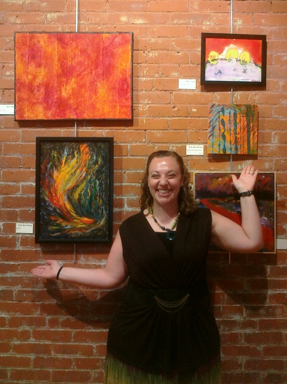 "The artist at The Elements Exhibition with her pieces, ""Windfire"" and ""It Happens When the Wind Changes"""