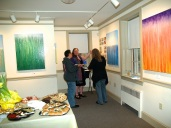 The artist Rachel Brask discusses her process with guests at exhibition opening of Abstracted Rainy Moments