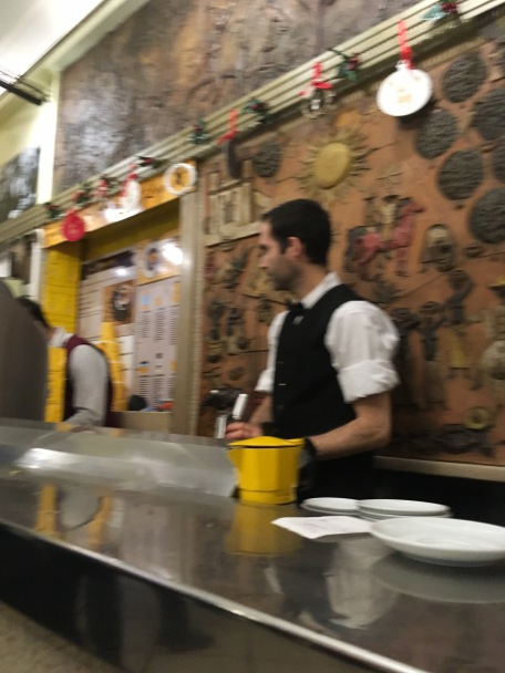 The barista and narrow bar at Sainte Eustachio Cafe