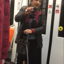 Lady singing on the train with her own speaker cart